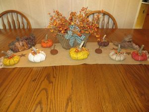Fall tablescape with fabric pumpkins and a basket of bittersweet.