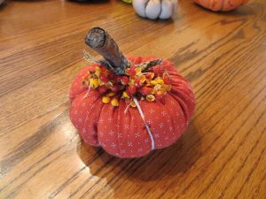 Close up of a fabric pumpkin with bittersweet.