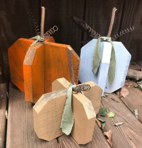 3 wooden pumpkins used as fall decoration on the porch.