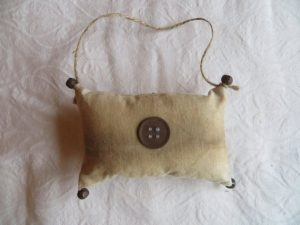 Simple primitive decorating. Coffee dyed muslin pillow ornie embellished with rusty pins or a rusty button and bells with hanger. Please specify which one. Dimensions- 3x5 inches. Made in the USA in a smoke free home.