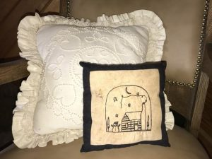 """Cute winter scene machine stitched on coffee stained muslin is great in your primitive Christmas decorating. This small pillow measures approximately 8 1/2"""" square. Throw it in with other pillows on a chair or couch for that perfect primitive accent. Or stand it up in the back of a shelf to add to a snowman shelf scrape. Made in the USA in a smoke free home. *Although all materials are washable, I don't recommend it as the coffee stain will be lifted from the fabric."""