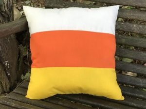 """Bright yellow, orange and white cotton fabric sewn in stripes to look like candy corn. Great fall decorating idea or Halloween decoration. Add it to your perfect spot for a great accent piece. Measures appropriately 12 1/2 x 12 1/2"""".Made in the USA in a smoke free home."""