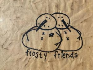 """Primitive decorating machine embroidered Frosty Friends picture in a painted black, wooden frame, glass covered. Primitive Christmas decorating idea. Frame size is approximately 9 1/2 x 11 3/4"""" inches and picture is 7 1/2 x 9 1/2"""" inches. Great simple picture to prop up on a shelf or use in a tablescape. It can also be hung on a wall. All items are USA made in a smoke-free home."""