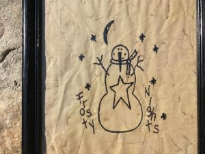 "Primitive Christmas snowman machine embroidered Frosty Nights picture in a painted black, wooden frame, glass covered. Great for primitive decorating. Frame size is approximately 9 x 11"" inches and picture is 7 1/2 x 9 1/2"" inches. Great simple picture to prop up on a shelf or use in a tablescape. It can also be hung on a wall. All items are USA made in a smoke-free home."