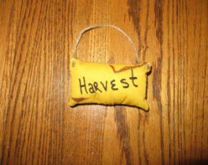 """These coffee stained fabric polyfiled pillows have jute hangers that can easily be removed turning the hangers into bowl fillers. Cute primitive decorating idea. Each machine embroidered word is available in 3 different colors. Approximately 2 1/2"""" x 4 1/2"""". Made in the USA in a smoke free home."""
