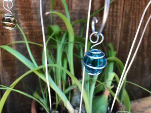 """Garden decoration for your potted plants. Marble wrapped in wire suspended from curled hook. Poke it in a plant for sparkle or use it in a fairy garden as lamp posts. They are 10"""" tall."""