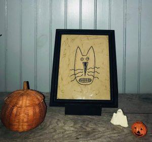 Embroidered cat face framed
