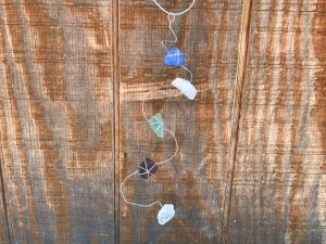 """Garden decorating idea. Man made sea glass wrapped with wire and bent into an abstract form. Each on is unique. Hang them in a tree or in a window or your very own special spot. It's sure to brighten up where ever you choose. Measures approximately 15"""" and 4"""" wide."""