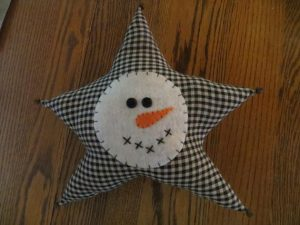 """Cute primitive Christmas decorating idea. These 12"""" x 12"""" star shaped pillow with smiling snowman face is made from cotton fabrics. The felt snowman face has been sprinkled with glitter to make it sparkle. Stuffed with polyfil. Rusty bells are sewn on all point to finish this rustic wintertime pillow. Available in black gingham. Made in the USA in a smoke free home."""
