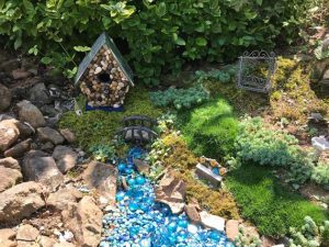 """My love of fairy gardens inspired me to take this simple wooden birdhouse and attached small, smooth stones to make a quaint fairy house. Makes an attractive addition to a fairy garden or use it on a shelf. Fits in perfectly as a primitive decorating idea. This cutie stands approx. 7 3/4"""" x 6"""" x 4"""". Made in the USA in a smoke free home."""