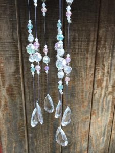 """Outdoor decorating. Shiny, sparkles radiate from this acrylic beaded sun catcher when the sun hits it just right. The base is an aluminum mold. Hang it from a hook or a tree branch and watch it twinkle. Measures 3 x 29""""."""