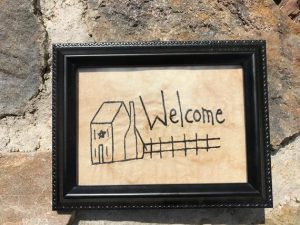 "Primitive machine embroidered Saltbox House with fence Welcome picture in a painted black, wooden frame, glass covered. Perfect primitive decorating idea. Frame size is approximately 6 1/2 x 8 1/2"" inches and picture is 4 1/2 x 6 1/2"" inches. Great simple picture to prop up on a table. All items are made in a smoke-free home."