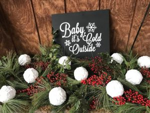 Baby It's Cold Outside sign in a greenery wagon